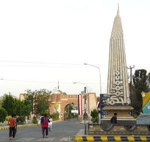 """Entrada de la Universidad de Saná. En el monumento se lee: """"Fe y Sabiduría""""."""